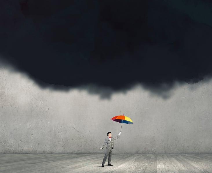 Businessman standing with umbrella under black cloud